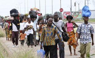 Des habitants fuient Abidjan, en Côte d'Ivoire, le 27 février 2011, après des affrontements entre les partisans de Laurent Gbagbo et d'Alassane Ouattara.