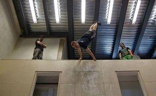 """Sous les voûtes de l'église Saint-Esprit de Québec, les acrobates de l'école du cirque de Québec font """"le grand saut"""" sur trampoline situé 5 mètres plus bas, rebondissent sur un trampoline et ricochent sur la paroi du mur."""