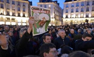 "A man holds up an edition of Charlie Hebdo magazine as people gather on the Place Royale in Nantes, western France,  on January 7, 2015, to show their solidarity for the victims of the attack by unknown gunmen on the offices of the satirical weekly Charlie Hebdo. Heavily armed men shouting ""Allahu Akbar"" stormed the Paris headquarters of a satirical weekly on  January 7, killing 12 people in cold blood in the worst attack in France in decades.    AFP PHOTO / GEORGES GOBET"