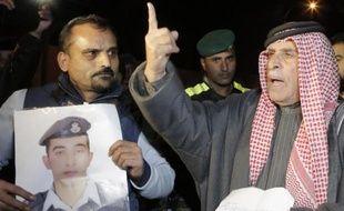 Le père d'un pilote jordanien menacé de mort par l'EI brandit sa photo le 28 janvier 2015 à Amman