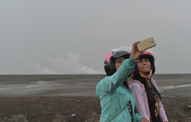 648x415 des touristes prennent des selfies le 28 mars 2016 devant le volcan de boue qui a devaste sidoarjo sur l ile de java en indonesie