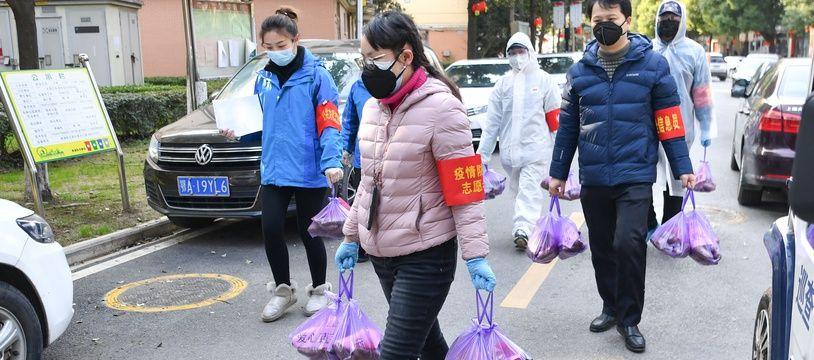 Des volontaires distribuent de la nourriture à Wuhan, le 23 février 2020.