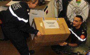 Des marins de la Marine nationale portant un carton avec des cadeaux de Noël pour les militaires à bord de la frégate Jean de Vienne le 22 décembre 2017 en méditerrannée orientale
