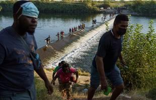 Des migrants haïtiens traversent le Rio Grande pour obtenir de la nourriture et des fournitures près du port d'entrée de Del Rio, à Ciudad Acuña, au Mexique, le 18 septembre 2021.