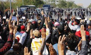 Des manifestants protestent devant une route bloquée par la police anti-émeutes à Mandalay, deuxième ville de Birmanie.