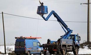 Des techniciens d'ERDF réparent une ligne électrique coupée par la neige à Ver-sur-Mer (Calvados), le 13 mars 2013.