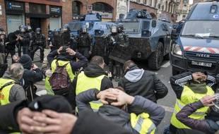 """Des """"gilets jaunes"""" symboliquement à genoux devant les blindés de la gendarmerie le 15 décembre 2018 à Toulouse."""