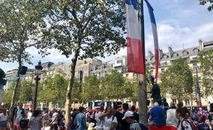 Des fans s'agglutinent le long de l'avenue des Champs-Elysées en attendant le passage du bus de l'équipe de France.