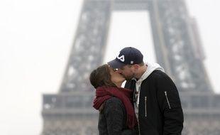 Un couple s'embrasse devant la tour Eiffel (image d'illustration).