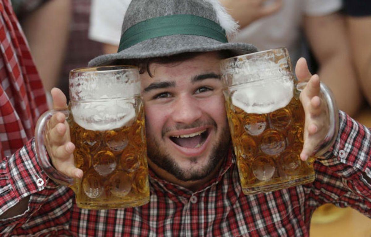 Un jeune homme pose avec ses deux pintes durant l'Oktoberfest de Munich, le 28 septembre 2014. – M.Schrader/AP/SIPA