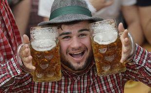 Un jeune homme pose avec ses deux pintes durant l'Oktoberfest de Munich, le 28 septembre 2014.