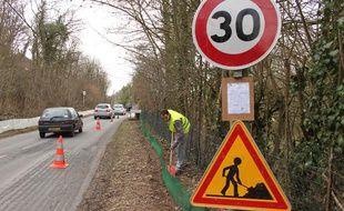 Sur la route communale d'Ormoy-la-Rivière (Essonne), des bénévoles installent une bâche pour éviter aux crapauds de se faire écraser, le 10 mars 2012.