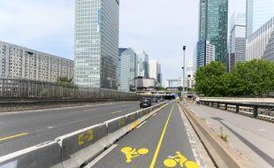 La piste cyclable provisoire Paris - La Défense avec un séparateur en béton.