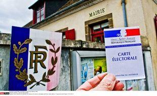 Carte d'électeur et panneau qui indique une mairie en campagne sarthoise, Sainte-Sabine, le 10 février 2014.