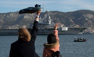 Des proches de l'équipage du «Charles de Gaulle» saluent le porte-avions lors de son départ.
