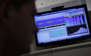Un homme étudie la voix d'un enregistrement téléphonique.