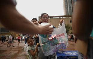 Des gens font la queue pour recevoir des vivres après les inondations à Zhengzhou, dans la province chinoise du Henan, le 22 juillet 2021.