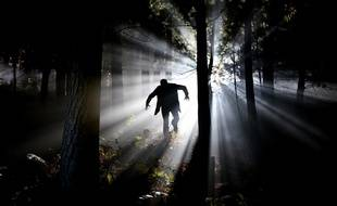 Illustration d'un homme courant dans les bois la nuit