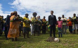 Emmanuel Macron plante un arbre.