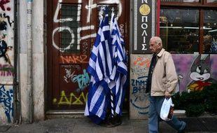 Un homme passe devant le drapeau grec au centre d'Athènes, le 29 octobre 2015
