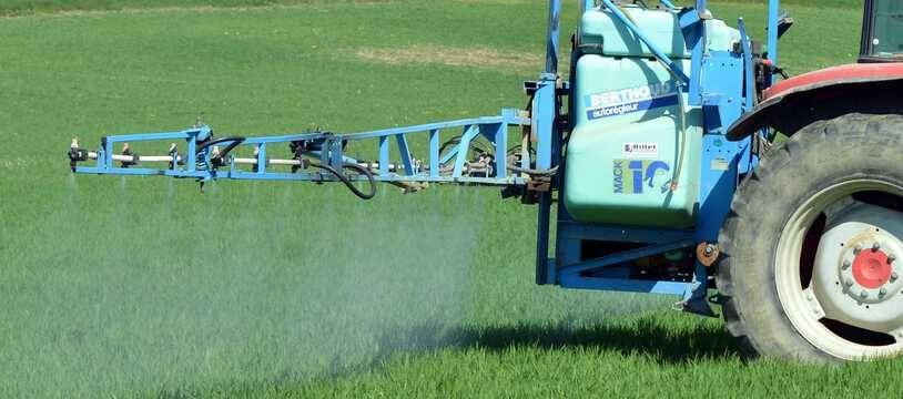 Illustration d'un tracteur pulvérisant un pesticide dans un champ.