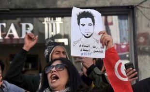 A Tunis, le 20 janvier 2016, une femme brandit le portrait de Ridha Yahyaoui, jeune chômeur de Kasserine décédé quelques jours plus tôt