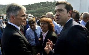 Le chancelier autrichien Werner Faymann (G) et le Premier ministre grec Alexis Tsipras (D) visitent un centre d'accueil pour les réfugiés à Mytilène, sur l'île grecque de Lesbos, le 6 octobre 2015