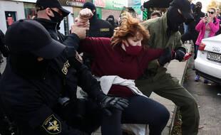 Des agents des forces de l'ordre arrêtent une participante à l'événement d'opposition Bright March for Women's Solidarity en dehors du marché de Komarovsky samedi 19 septembre.