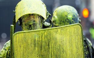 Des policiers sont recouverts de peinture jaune, samedi 1er décembre, à Paris.