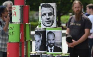 """Des canettes avec le visage d'Emmanuel Macron et Edouard Philippe à la """"marée populaire"""" à Paris le 26 mai 2018."""