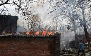 Un pompier passe devant un bâtiment en feu suite à un bombardement ayant touché plusieurs maisons dans la ville ukrainienne de Donetsk, le 3 février 2015