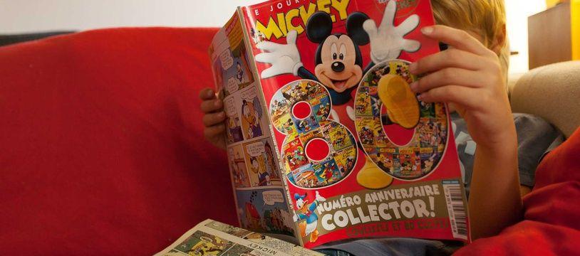 Un enfant lit le «Journal de Mickey» (illustration).