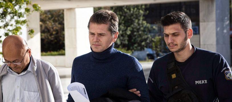 Alexander Vinnik (au centre), escorté par la police grecque, en décembre 2017, peu après son arrestation.