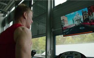 Capture d'écran d'une vidéo montrant l'astronaute britannique Tim Peake courir sur un tapis, virtuellement immergé dans le marathon de Londres grâce à un écran posé devant lui.