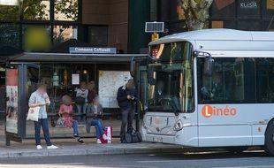 Des passagers à un arrêt de bus à Toulouse.