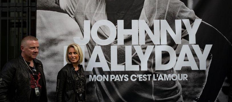 Des membres du fan club de Johnny Hallyday devant un poster de son album posthume «Mon Pays c'est l'amour».