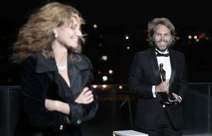 """Florian Zeller sourit à Marine Delterme alors qu'il tient sa statuette près avoir remporté le meilleur scénario adapté pour le """"The father'' lors d'une projection des Oscars, le lundi 26avril 2021 à Paris, en France."""