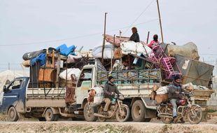 Des camions transportant meubles, matelas et couvertures près d'un camp de déplacés fuyant l'avancée des troupes syriennes dans les provinces d'Idleb et d'Alep, le 16 février 2020.