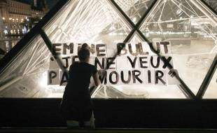 Une femme colle des affiches contre les féminicides sur la pyramide du Louvre à Paris, le 14 septembre 2019.