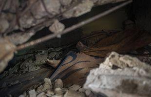 Le corps d'un Palestinien repose sous les décombres d'un bâtiment qui a été détruit lors des frappes aériennes israéliennes dans la ville de Gaza, le 16 mai 2021.