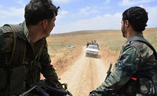 Syrian regime forces drive on May 9, 2015 near Assal al-Ward, a small regime-controlled village situated on the mountain of al-Kanissa in the Qalamun region, after they seized control of several hilltops in the mountainous area that straddles the Syria-Lebanon border with the support of Lebanon's Shiite Hezbollah movement. Pro-government forces have been battling rebel groups and Al-Qaeda affiliate Al-Nusra Front in the Qalamun region, which lies north of Damascus. AFP PHOTO / STR