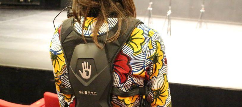 Fixé et sanglé sur le dos, le Subpac est connecté à la régie son par un boîtier qui retranscrit les sons par vibrations.