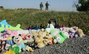 Des soldats prorusses passent à proximité d'un mémorial aux victimes du vol MH17, le 17 juillet 2016, sur le lieu du crash près du village de Grabove, dans l'est de l'Ukraine