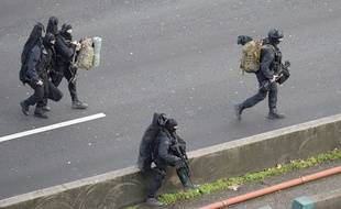 """Members of the French police special force RAID walk with their equipment on the """"peripherique"""" (circular road) in Saint-Mande, near Porte de Vincennes, eastern Paris, on January 9, 2015 to take their positions after at least one person was injured when a gunman opened fire at a kosher grocery store on January 9, 2015 and took at least five people hostage, sources told AFP. The attacker was suspected of being the same gunman who killed a policewoman in a shooting in Montrouge in southern Paris on January 8.  AFP PHOTO / ERIC FEFERBERG"""