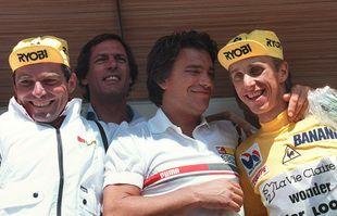 Le 21 juillet 1986, les deux cyclistes Bernard Hinault et Greg Lemond sont avec Bernard Tapie sur le podium de la 21e étape du Tour de France entre Briançon et L'Alpes d'Huez.
