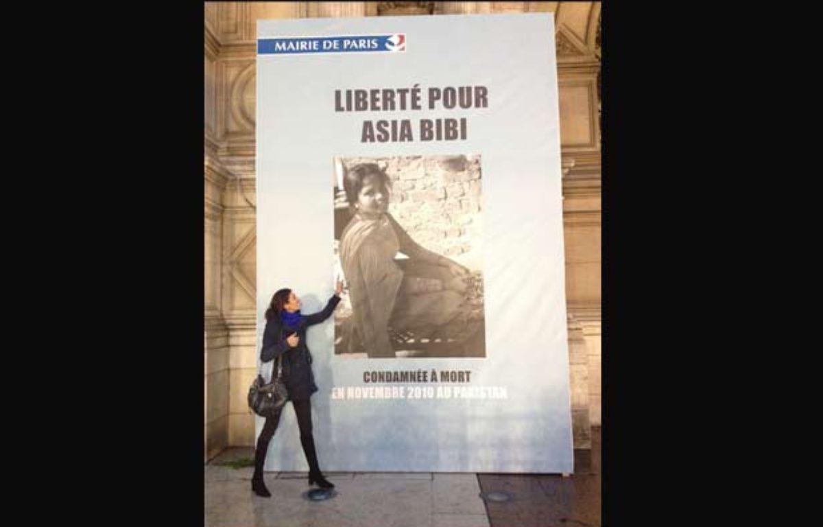 La journaliste Anne-Isabelle Tollet devant la photo d'Asia Bibi affichée à l'hôtel de ville de Paris, en décembre 2014. – éd.du Rocher