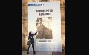 La journaliste Anne-Isabelle Tollet devant la photo d'Asia Bibi affichée à l'hôtel de ville de Paris, en décembre 2014.