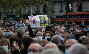 Un homme brandit un numéro du journal Charlie Hebdo lors du rassemblement en hommage à Samuel Paty le 19 octobre à Paris.