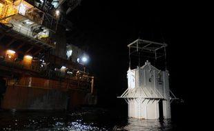 Le «couvercle» visant à colmater la fuite de pétrole qui s'écoule de la plate-forme Deepwater Horizon, au début de sa descente dans le Golfe du Mexique, au large des côtes de Louisiane, le 6 mai 2010.