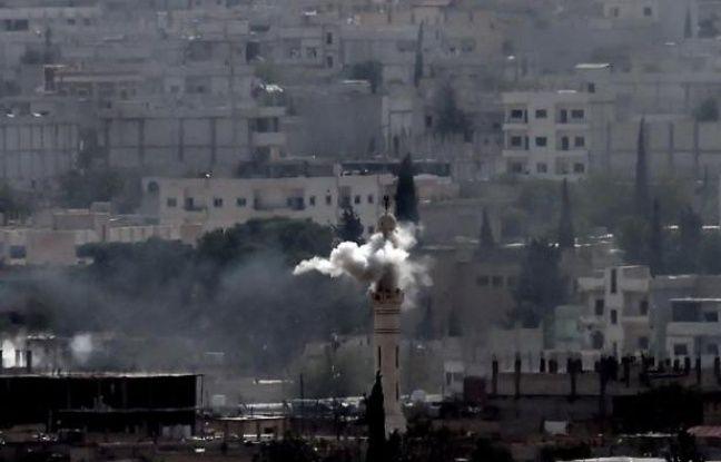De la fumée s'élève d'un minaret après une nouvelle salve de bombardements sur la ville kurde de Kobané, le 13 octobre 2014
